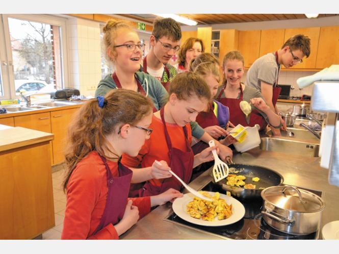 Mädchen und Burschen entdecken bei Magdalena Wöckel (im Hintergrund) bei diesem Projekt nicht nur den Spaß am Kochen, sondern sie verbessern ihre Fähigkeiten und erarbeiten die Rezepte für ein Jugendkochbuch. Foto : schlecker
