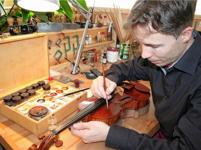 Sorgfalt und ein gutes Augenmaß: Bei der Lackretusche bringt Bernd Ellinger alte Instrumente wieder auf Hochglanz. Lezius-Pratsch