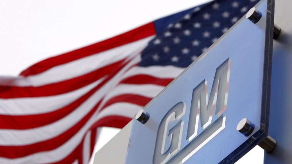 Die US-Flagge weht in Detroit hinter dem Logo des Automobilkonzerns General Motors. Foto: Jeff Kowalsky/epa